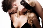man sensually dominates his woman lover with blindfold